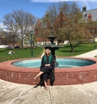 Allison Betelak sits on a brick park fountain in her graduation gown with her legs crossed and is smiling