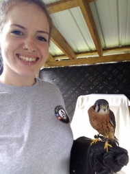 Anastasia is taking a selfie of her holding a bird, she is smiling and wearing her gray americorps t-shirt