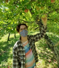 Benjamin is picking an apple with a blue and orange polka dotted mask, a striped shirt and a green flannel with his americorps pin