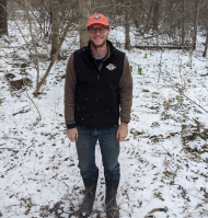 John Plummer stands in the snow with an orange AmeriCorps ball cap and a Green Mountain Club fleece vest on