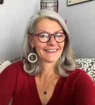 Mary is smiling in her house, she is wearing a red sweater, has chunky hooped earrings, red glasses, and long gray hair